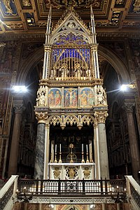 The high altar and the 14th-century Gothic ciborium. The relic of the original wooden altar used by St Peter comprises the high altar. Above the ciborium are Sts Peter and Paul.